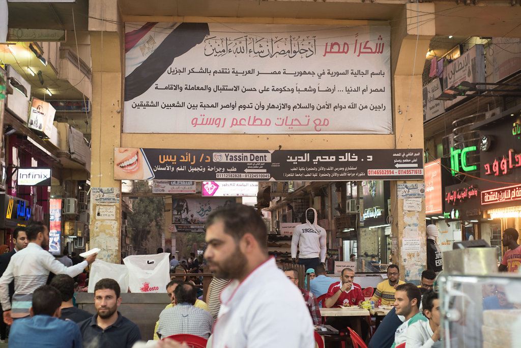 """A note of """"thanks"""" to Egypt is one of the first things one sees upon walking into the Syrian street. The note reads, """"On behalf of the Syrian delegation in the Arab Republic of Egypt, we offer thanks to Egypt the mother of the world… land, people, and gov"""