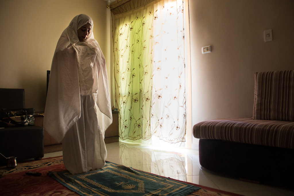 Leena's mother prays at home. She too says she has gotten accustomed to life in Egypt, and is happy with where her family lives. It is a bit more expensive that other places in 6th of October city, but everything is easily accessible, and her husband who