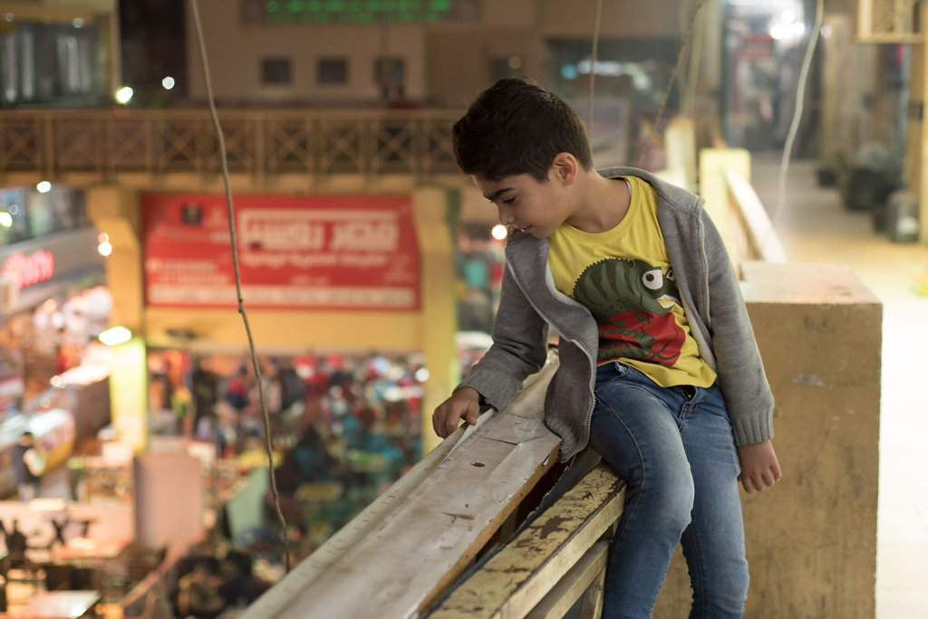 Gyath looks down at the Syrian street, where he spends a lot of time at his father's sweet shop and playing with his neighbors.