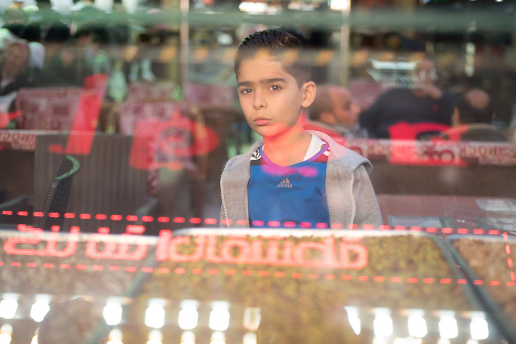 """Gyath looks through the sweets displayed in the glass adorning his father's shop in the """"Syrian street."""""""