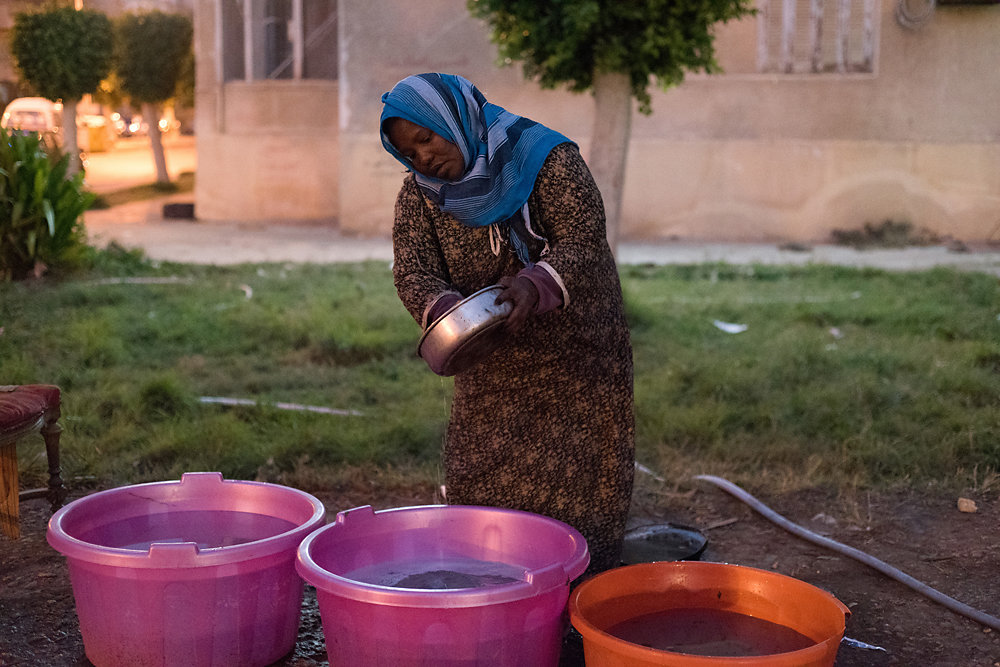 Sa'eeda washes some dishes in the buckets of water that have been collected and placed in the garden. She later put some yogurt in the plate for the children to eat with bread.