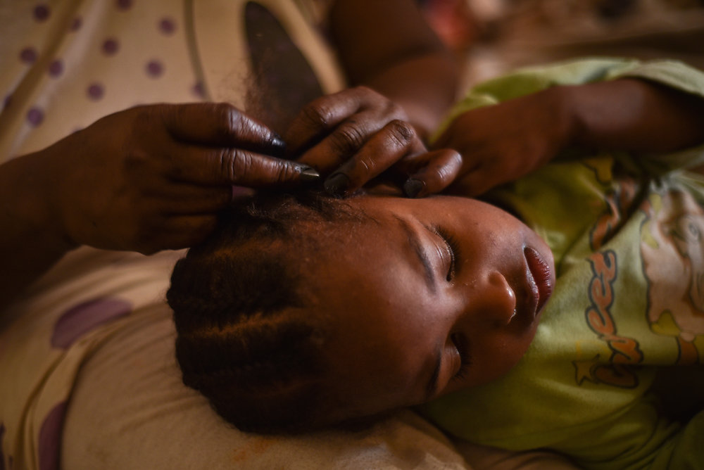 Sa'eeda fixes her daughter Ekram's hair before going off to work.